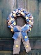 Výrobek: Věnec z pytloviny dekorován riflovinou, žlutými květy a dřevěnými kolíčky