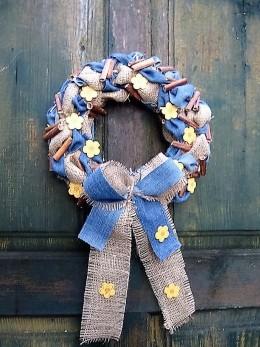 Obrázek výrobku: Věnec z pytloviny dekorován riflovinou, žlutými květy a dřevěnými kolíčky